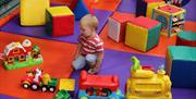 Indoor play area with child on mat surrounded by toys