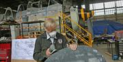 Image is of a man working on a plane part
