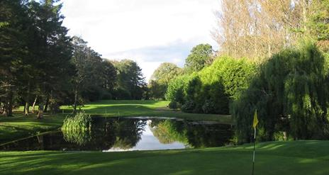 Image is of golf course with lake around it
