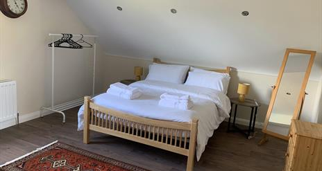 Image shows bedroom in loft with double bed, dressing mirror and clothes rail