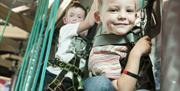 Image is a close up of 2 boys on a climbing frame