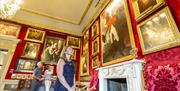 Image shows visitors viewing various paintings on the wall in one of the visiting rooms