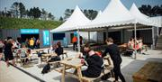 Image shows outside seating area with people eating and drinking at picnic tables