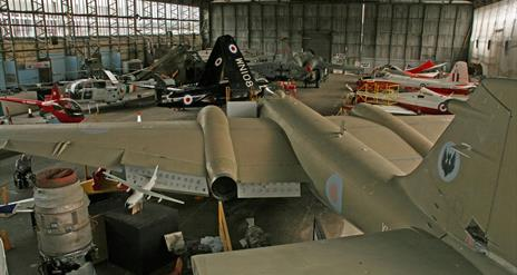 Image is of various types of aircraft in a hangar