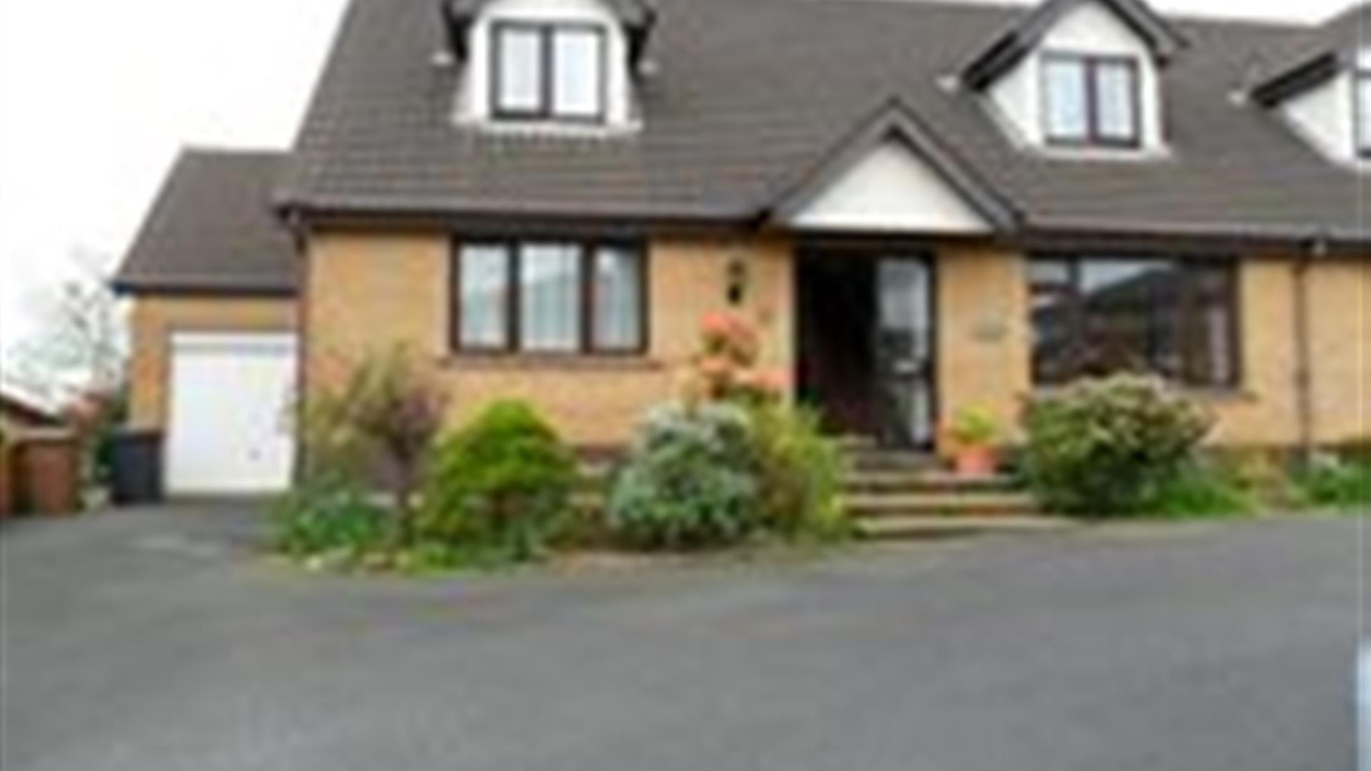 Image shows front of property with a few low steps and tarmac driveway