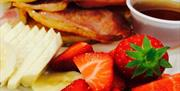 Image is off sliced banana, strawberries, bacon and maple syrup