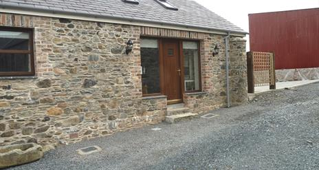 Image shows stone cottage with wooden front door and gravel drive way