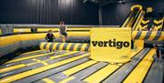Image is of the large inflatables and children jumping on to them. The word Vertigo is branded on the inflatable.