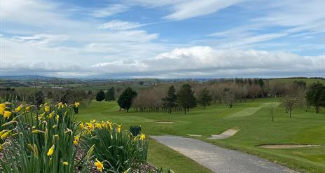 Image shows golf course, walking path and view of countryside beyond