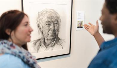 A couple converse in front of a sketch of Heaney