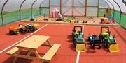 Indoor Soft play area with child sized dumper trucks and a picnic bench