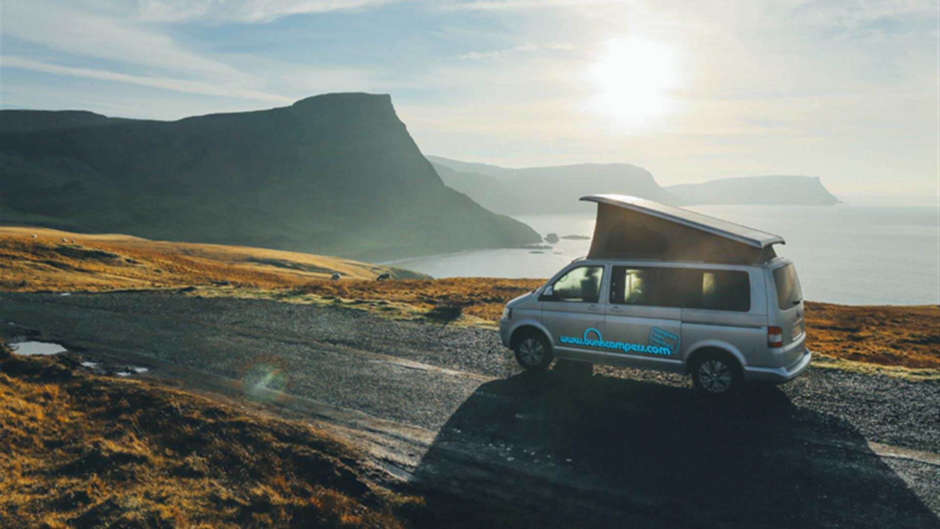 Image is of campervan driving down a road with sea and mountains in view