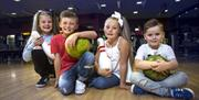 Image is of children sitting on the ground holding bowling bowls inside the bowling alley