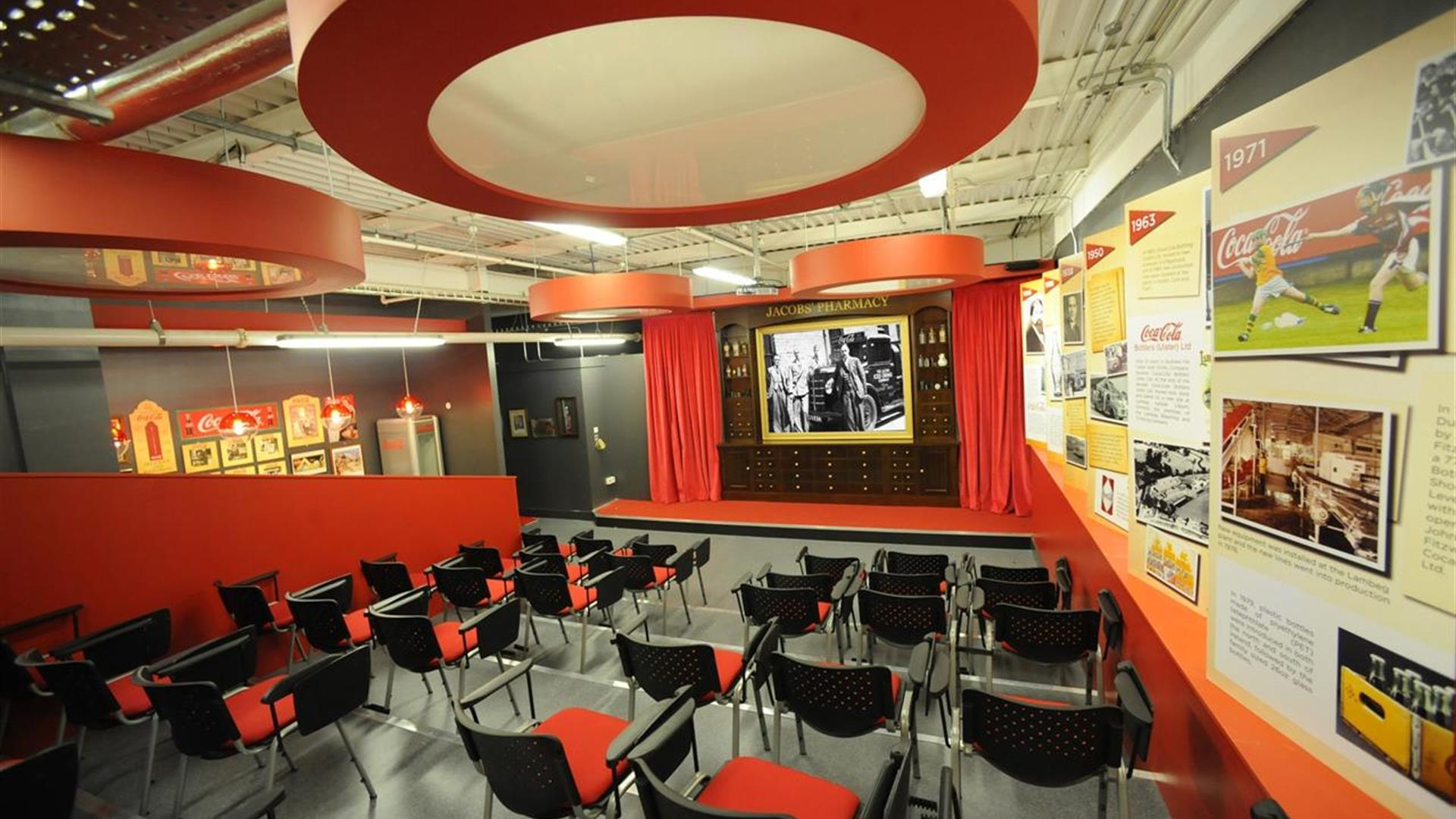 Image is of a meeting room with lots of chairs, images on the walls and large film screen on a stage