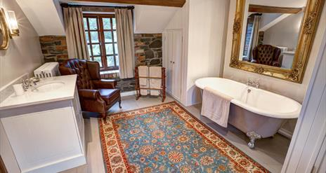 Image shows large bathroom with roll top bath and large mirror above it. Large rug. armchair, wash basin with storage underneath