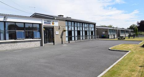 Image is of front of the building with tarmac driveway and grass area beyond