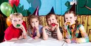 Image is of children sitting at a table with party hats on