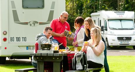 Image shows family and friends sitting at picnic table with caravan in the background