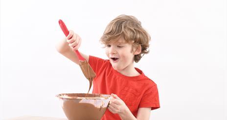 Boy enjoys mixing chocolate at The Chocolate Manor