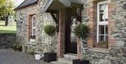 Image shows outside of stone property with bay tree plants at either side of front door