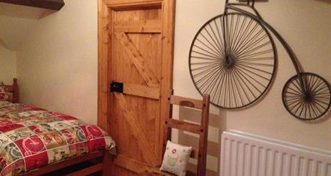 Image shows bedroom with pine door and replica penny farthing bicycle on the wall