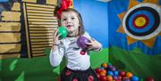 Image is of a young girl playing with coloured balls in a pen