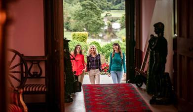 Three girls walking through the doors of Killymoon Castle