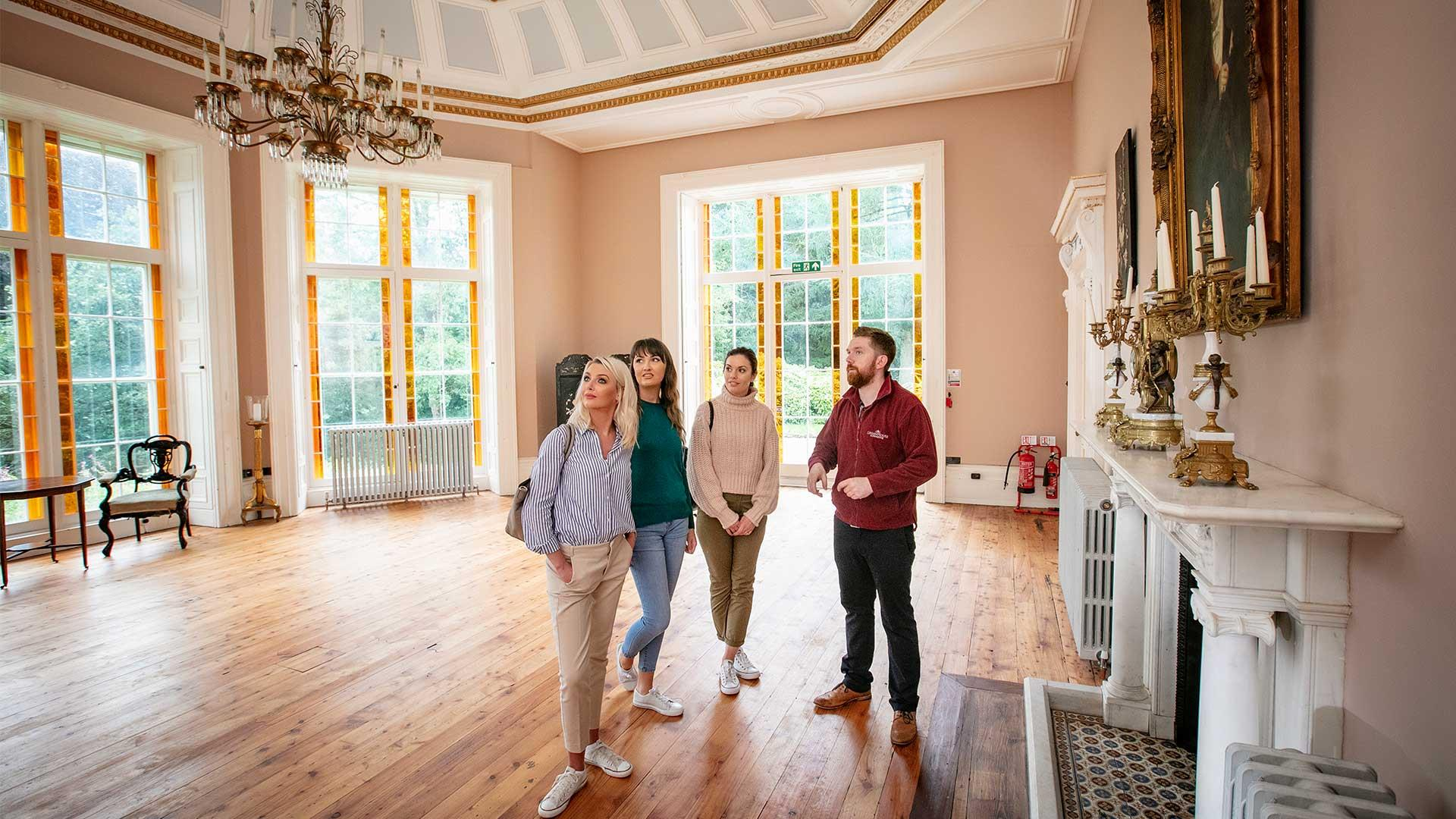 Three ladies stand with a tour guide inside the ballroom of Lissan House.