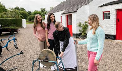 Girls pictured with a woman in period dress outside an old thatched cottage with a red door