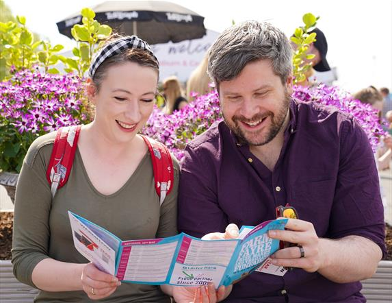Couple reading the brochure for the show