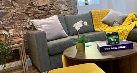 Image shows lounge area with sofa, foot stool, exposed brick wall with 2 clocks showing the time in Comber and New York. Wooden flooring and coffee ta