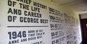 White wall painted with George Best football facts