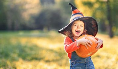 A young girl wearing a witch's hat and holding a pumpkin. The girl is smiling.