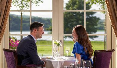 A male/female couple dining at the Catalina Restaurant at Lough Erne Resort, Enniskillen, County Fermanagh. They are sitting beside French doors overlooking Lough Erne.