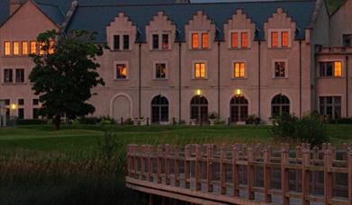 An exterior shot of Lough Erne Resort at dusk with some windows illuminated by interior lighting. A bridge is in the foreground.