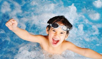 A young boy splashing in a swimming pool, surrounded by bubbles and wearing goggles on his forehead.