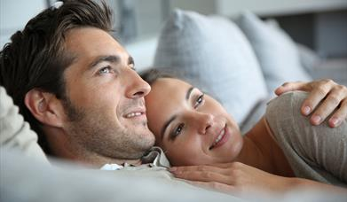 A male/female couple lying on top of a bed with arms around each other. Both are smiling and looking at something out of shot.