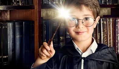 A child dressed as Harry Potter, wearing a black gown, holding a glowing magic wand and wearing glasses, standing in front of a book case