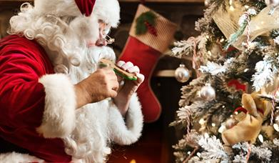 Santa Claus sitting beside a Christmas tree in front of a decorated fireplace, eating gingerbread and drinking a glass of milk.
