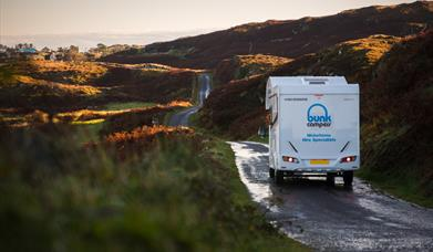 A campervan driving along a narrow road through rugged and hilly terrain on a wet day