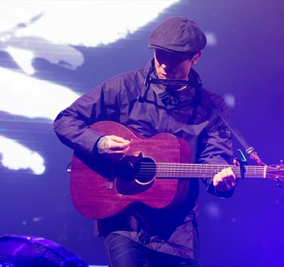 Gerry Cinnamon playing guitar and singing.