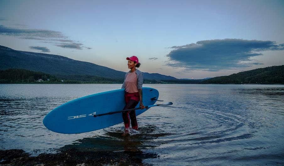 Sommerkveld. Person med padlebrett går inn på land fra innsjø,