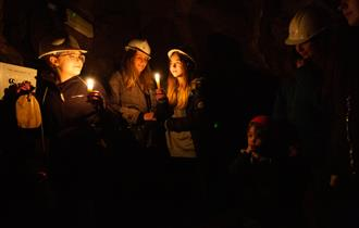 Photo is of a group of people in the dark in Temple Mine. The only light is from the  lit candles they are holding close to their faces.