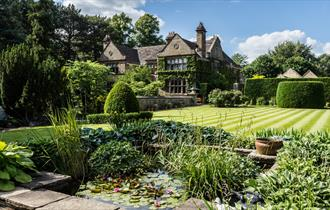 Image of the pond and gardens at Fischer's with the hall in the background.