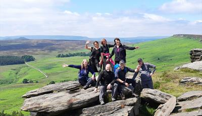 A group standing on Stanage Edge overlooking the Hope Valley
