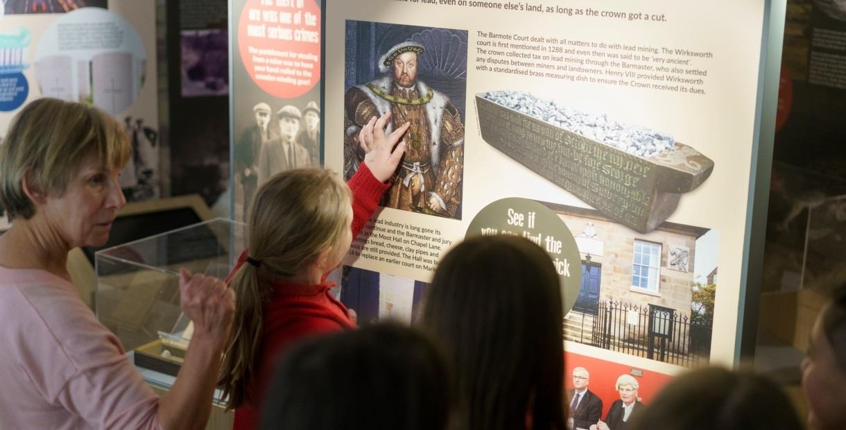 A lady and some children look at a display about lead mining in Wirksworth.