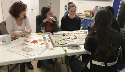 Photo of 5 people playing a board game