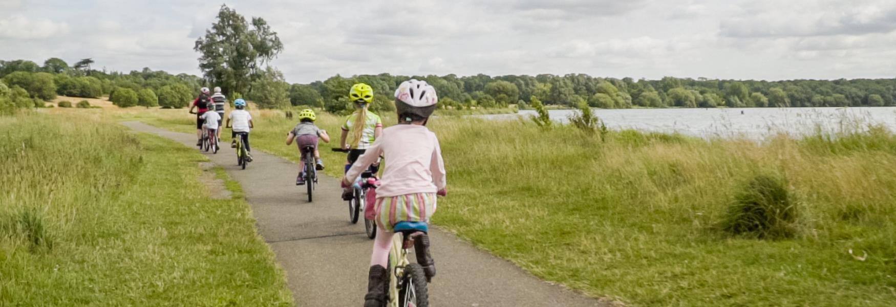 A family cycling around Nene Park.