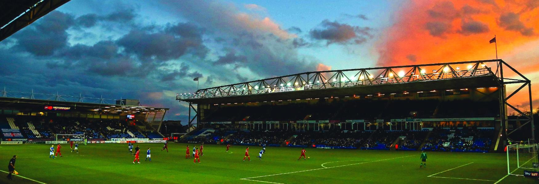Image of a football match being played at London Road Football Stadium.