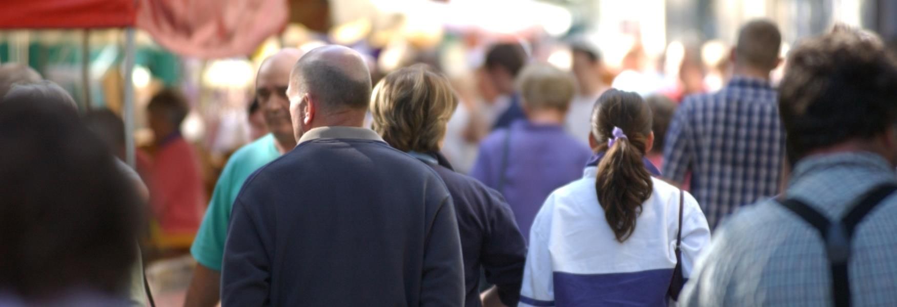 Image of people looking at a variety of street market stalls.